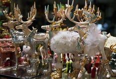 Het venster van de Kerstmiswinkel met een met de hand gemaakte inzameling van rendier seizoengebonden speelgoed en decoratie stock foto's