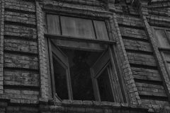 Het venster van het oude griezelige verlaten enge huis waarin het leven een Spook en een moord Stock Foto's