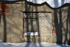 Het venster van het oude baksteengebouw in gebarsten die pleister met ijzer roestige rooster wordt behandeld, schaduwen van bomen stock foto's