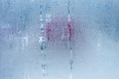 Het vensterglas met condensatie, sterke, hoge vochtigheid in de ruimte, grote waterdruppeltjes stroomt onderaan, koude toon stock afbeeldingen