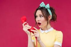 Het verbaasde geschokte jonge vrouw spreken op telefoon met rood ontvangt Royalty-vrije Stock Afbeeldingen