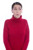 Het verbaasde kijken jonge vrouw in rode die trui - over wit wordt geïsoleerd Stock Afbeelding