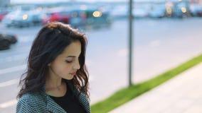 Het verbazen van donkerbruin haired meisje in strikt grijs jasje en zwarte kleding die iets op haar smartphone op stedelijk onttr stock videobeelden