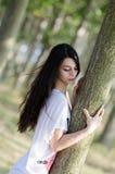 Het verbazen van donkerbruine dame met lang krullend haar, vrouw die op boom leunen Stock Afbeeldingen
