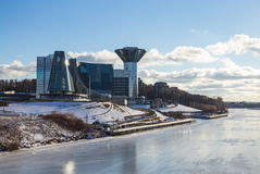 Het verbazen weerspiegelde het voortbouwen op de banken van de bevroren rivier op een Zonnige dag Stock Foto