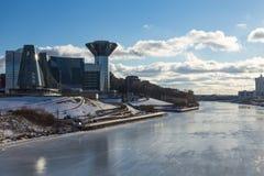 Het verbazen weerspiegelde het voortbouwen op de banken van de bevroren rivier op een Zonnige dag Stock Foto's