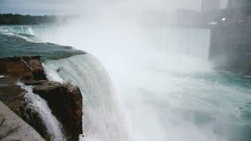Het verbazende close-upschot die van vogel door woedende waterstroom vliegen die onderaan een rots in epische Niagara meeslepen v stock videobeelden