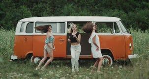 Het verbazende drie dames bewegen zich zeer charismatisch in een dans voor een oranje uitstekende bestelwagen stock footage