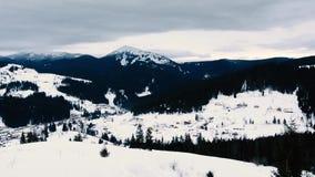 Het verbazende landschap waarop de ochtend in een bergsneeuw wordt ontspannen behandelde Oekra?ens dorp stock footage