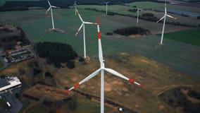 Het verbazende luchtclose-upschot, die boven windmolenturbines vliegen bewerkt op de herfstgebied, ecologische stroombronnen stock footage