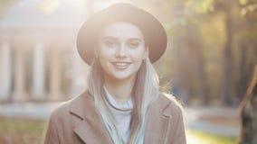 Het verbazende meisje die in laag met zwarte hoed de parksteeg, onderzoekend de camera en geeft verbazende glimlach terugtrekken  stock videobeelden
