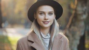 Het verbazende meisje die in laag met zwarte hoed de parksteeg, onderzoekend de camera en geeft verbazende glimlach terugtrekken  stock footage