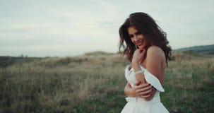 Het verbazende meisje die met perfecte glimlach in het midden van landschapsclose-up, kleedde zich in witte kleding glimlachen stock footage