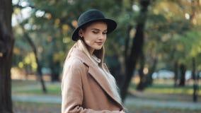Het verbazende meisje in een romantische blik, met zwarte hoed die onderaan de parksteeg lopen, onderzoekend de camera en geeft h stock footage