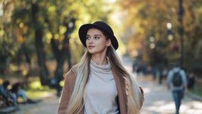 Het verbazende meisje in een romantische blik, met zwarte hoed die onderaan de parksteeg lopen, onderzoekend de camera en geeft h stock videobeelden