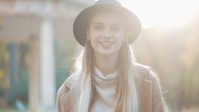 Het verbazende meisje in een romantische blik, met zwarte hoed die onderaan de parksteeg lopen, rond kijkend en geeft verbazende  stock video