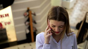 Het verbazende meisje met rode lippen en rood nagellak spreekt op haar celtelefoon in een wandelgalerij stock video