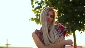 Het verbazende portret van mooi blondemeisje met schitterend lang haar bekijkt camera en het leuke glimlachen stock video