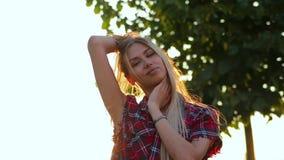 Het verbazende portret van mooi blondemeisje met schitterend lang haar bekijkt camera en het leuke glimlachen tegen zonlicht stock video