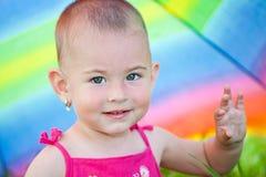 Het verbergen onder een kleurrijke paraplu Stock Afbeeldingen