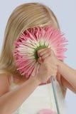 Het verbergen van het meisje achter roze bloem Stock Foto's