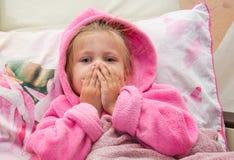 Het verbijsterde meisje in bed onderzoekt de camera stock afbeelding