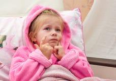 Het verbijsterde meisje in bed onderzoekt de camera royalty-vrije stock afbeelding