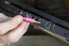 Het verbinden van de rode cinch stop met de microfoonhefboom op laptop stock foto's