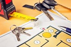 Het verbinden van nieuwe sleutel op projectplan van flatgebouw stock afbeelding