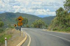 Het verdraaien van asfaltweg in berg De gele gevaarlijke draai van de verkeerstekenaandacht, kronkelweg stock afbeelding