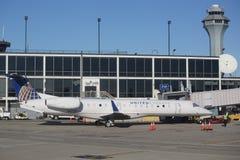 Het verenigde Uitdrukkelijke vliegtuig van Embraer op tarmac bij O'Hare Internationale Luchthaven in Chicago stock foto's