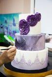 Het verfraaien van de kleuring van de huwelijkscake door borstel royalty-vrije stock afbeeldingen