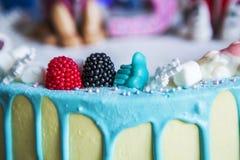 Het verfraaien van een cake met bessen, suikergoed Op de blauwe stroken van de cakeglans Stock Foto's