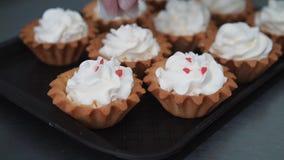 Het verfraaien van kop-cake met room Het gebruiken van kokende zak, banketbakker die veelkleurige cupcakes voor partij maken Gesc stock videobeelden