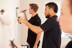 Het verfraaien van team die een ruimte in een huis schilderen stock foto's