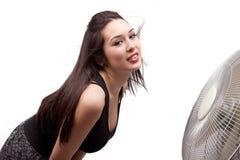 Het verfrissen van de vrouw zich voor grote ventilator stock afbeelding