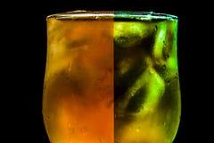 Het verfrissen van kleurrijke drank in glas met ijs op een zwarte achtergrond Stock Foto