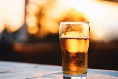 Het verfrissen van Koud Lager Beer Laying On Table tegen Hemel tijdens Zonsondergang Royalty-vrije Stock Afbeelding