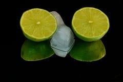 Het verfrissen zich, twee halfs van groene kalk en twee ijsblokjes Royalty-vrije Stock Foto's