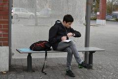 Het vergeten schoolthuiswerk, jongen controleert de tijd tot de bus zal aankomen stock afbeelding