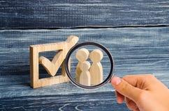 Het vergrootglas bekijkt de Drie houten menselijke cijferstribune samen naast een tik in de doos Het concept verkiezingen royalty-vrije stock fotografie