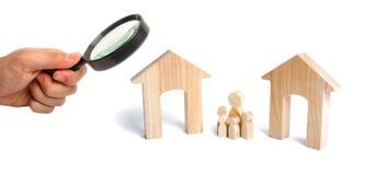 Het vergrootglas bekijkt de familie met kinderentribune tussen twee huizen de benoeming van de toekomstige familie royalty-vrije stock afbeeldingen