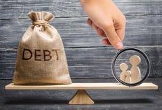 Het vergrootglas bekijkt de familiecijfers en een zak met de inschrijvingsschuld op de schalen leningslast op families royalty-vrije stock foto's