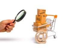 Het vergrootglas bekijkt de Supermarktkar met dozen, koopwaar: het concept het kopen van en het verkopen van goederen en diensten royalty-vrije stock foto's