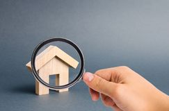 Het vergrootglas bekijkt een klein houten woonhuis op een grijze achtergrond Hypotheek en krediet voor de aankoop stock afbeelding