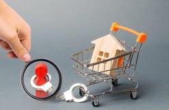 Het vergrootglas bekijkt een persoon de handboeien om:doen aan een huis op een supermarktkar Financi?le afhankelijkheid, niet bes stock foto