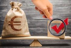 Het vergrootglas bekijkt een zak met euro geld en een rood vinkje van een stem op schalen Interventie in politiek royalty-vrije stock foto