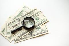 Het vergrootglas ligt op Amerikaanse die dollars op witte achtergrond worden geïsoleerd stock foto