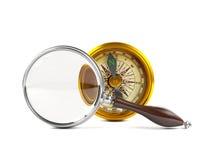 Het vergrootglas onderzoekt gouden kompas Royalty-vrije Stock Foto's