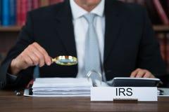 Het Vergrootglas van auditorexamining documents with bij Lijst Stock Afbeelding